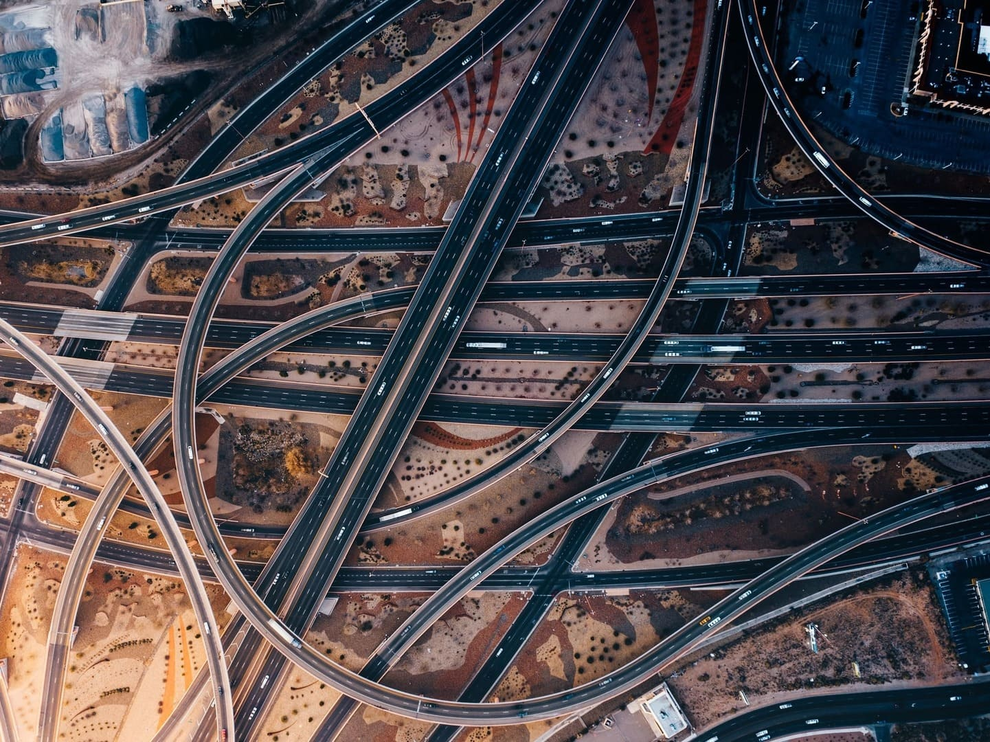 Drone image of many roads and overpasses winding past each other with vehicles travelling on them.